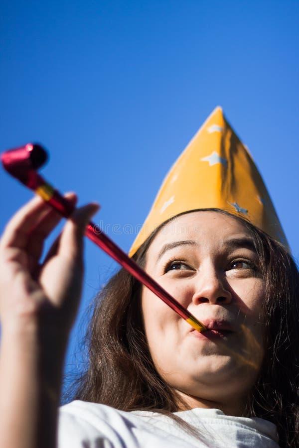 戴党帽子的可爱的少妇欢呼和庆祝吹的党垫铁 吹在党口哨a的滑稽的可爱的女孩 图库摄影