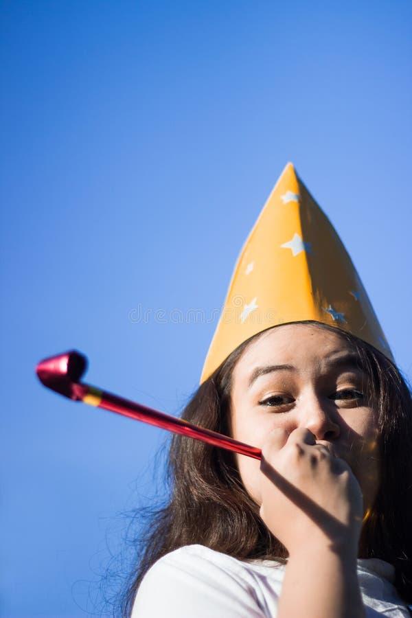戴党帽子的少妇欢呼和庆祝吹的党垫铁 吹在党口哨和拷贝sp的滑稽的可爱的女孩 免版税库存照片