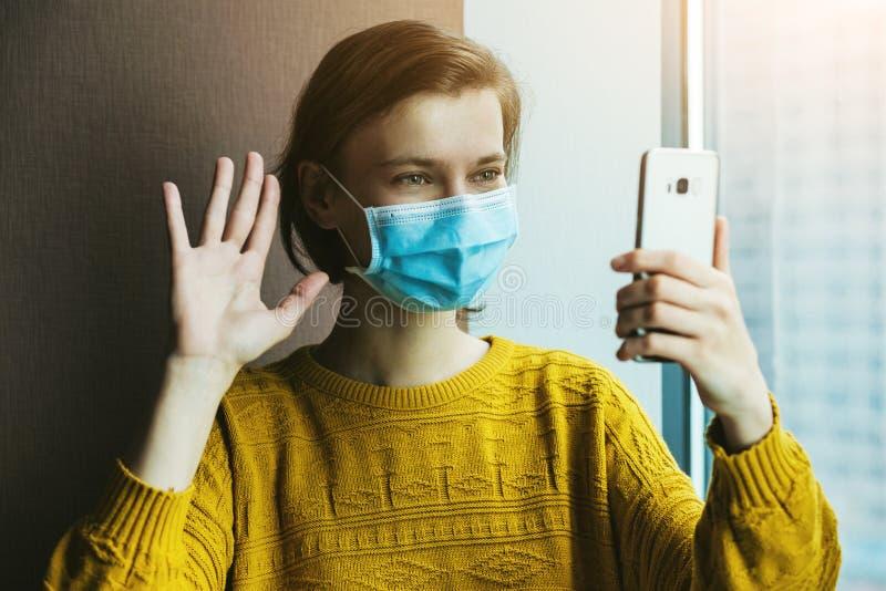 戴医用口罩的女子在家居隔离处使用电话 库存图片