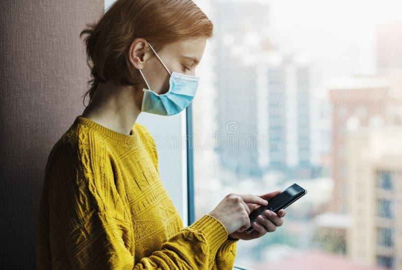 戴医用口罩的女子在家居隔离处使用电话 免版税库存照片