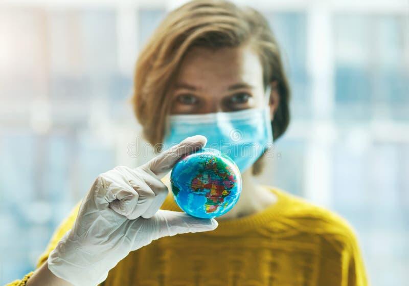 戴医用口罩的女子手戴手套,手持全球地球模型 库存照片