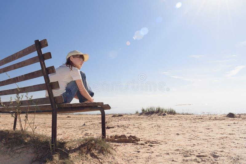 戴哀伤地选址在海岸的一条长凳和神色的眼镜的孤独的女孩入距离 库存照片