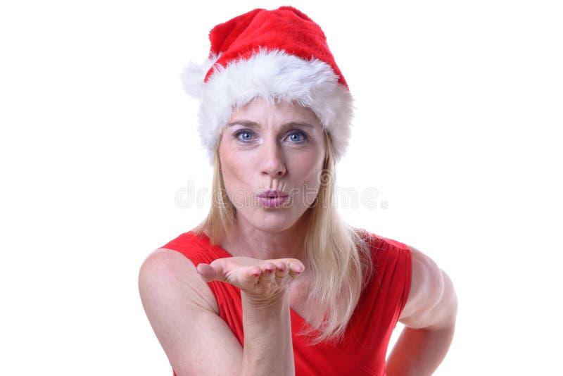 戴圣诞老人帽子和送飞吻的妇女 免版税库存图片