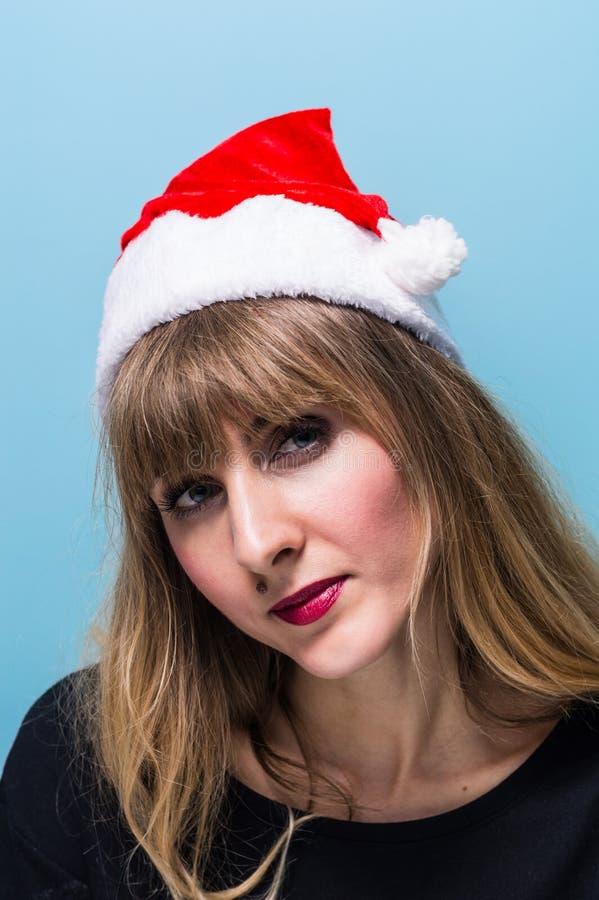 戴圣诞老人帽子的一个美丽的白肤金发的女孩的画象 免版税图库摄影