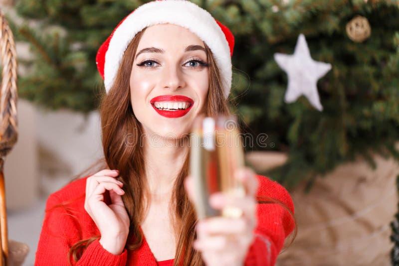 戴圣诞老人帽子的可爱的圣诞节妇女说多士和饮用的香宾 图库摄影