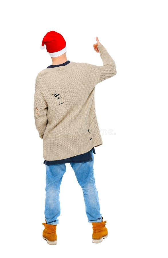 戴圣诞老人帽子的后面观点的一个人显示他的拇指u 库存图片