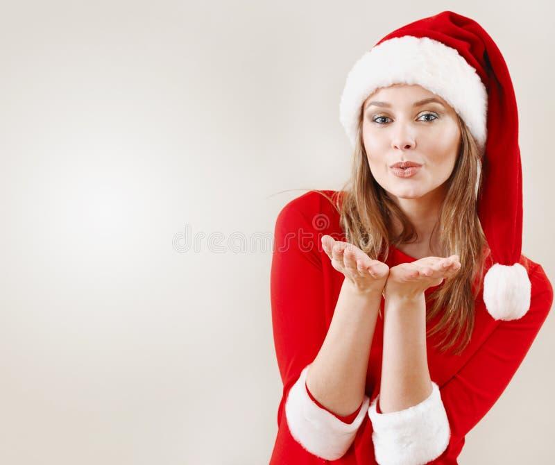 戴圣诞老人帽子的圣诞节妇女送飞吻 库存照片