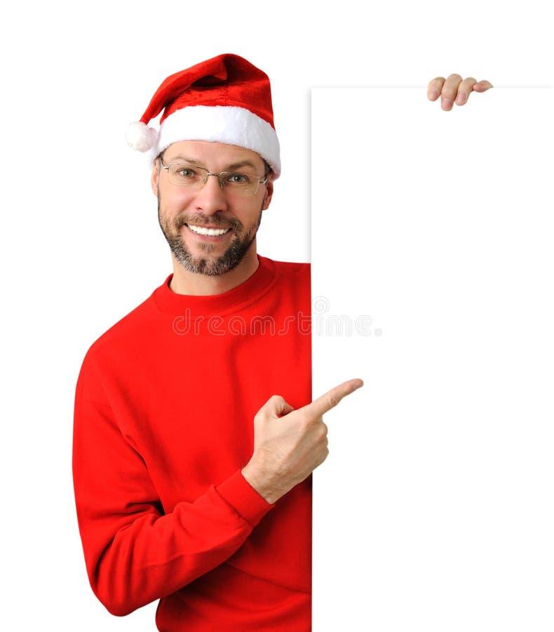 戴圣诞老人帽子的微笑的圣诞节人 免版税图库摄影