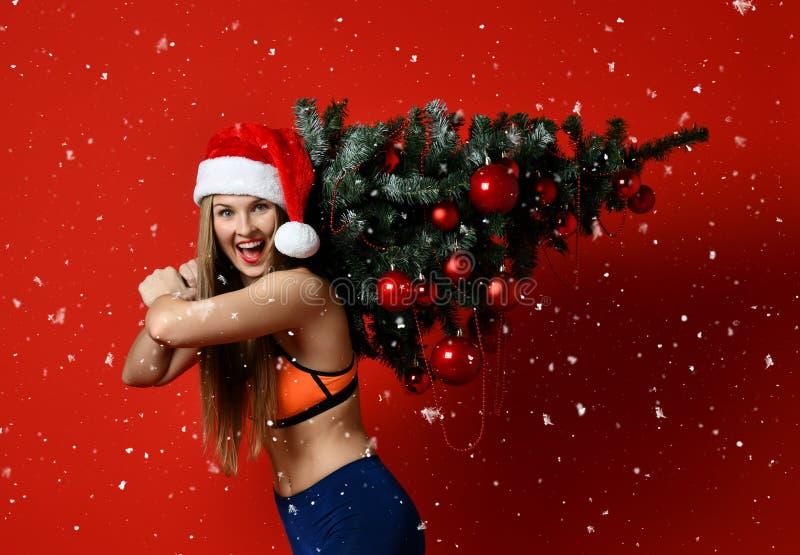 戴圣诞老人帽子的性感的圣诞节健身体育妇女拿着在她的肩膀的xmas树 库存照片