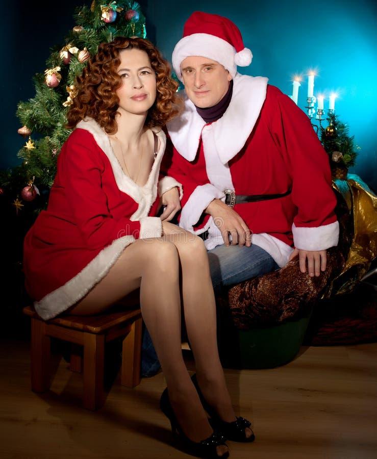 戴圣诞老人帽子的愉快的成熟夫妇临近圣诞树 库存照片
