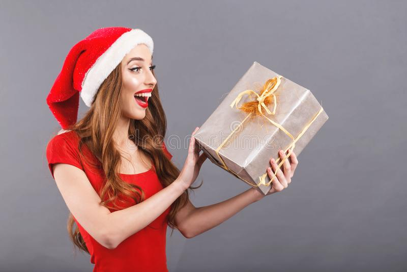 戴圣诞老人帽子的激动的圣诞节妇女惊奇礼物 库存图片