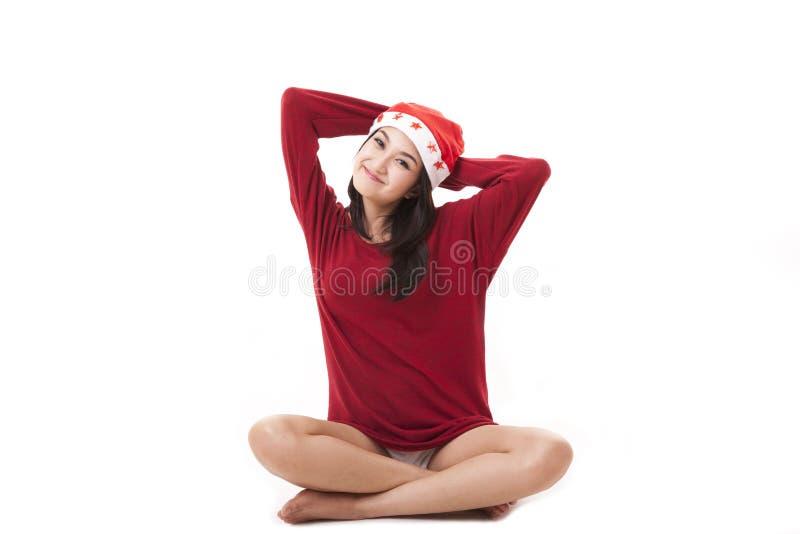 戴圣诞老人帽子的美丽的亚裔妇女愉快地微笑 库存照片