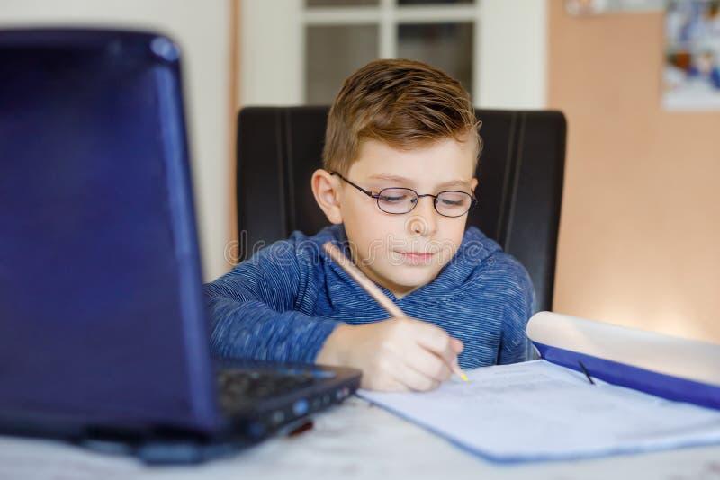 戴在家做学校家庭作业与笔记本的眼镜的愉快的健康孩子男孩 感兴趣的儿童文字杂文与 图库摄影