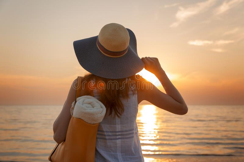 戴在日落轻看的年轻和美丽的妇女一个帽子 库存图片