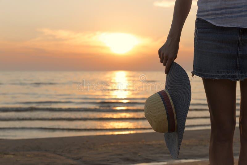 戴在日落轻看的年轻和美丽的妇女一个帽子 免版税库存照片
