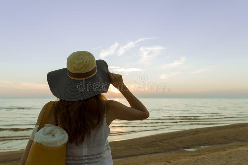 戴在日落轻看的年轻和美丽的妇女一个帽子 库存照片