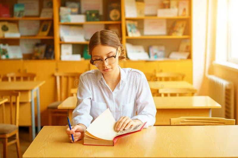 戴坐在一张桌上在办公室和读书的眼镜的年轻美丽的学生 免版税图库摄影