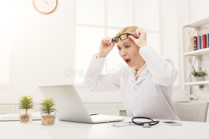 戴坐在桌面的眼镜的震惊医生 免版税库存图片