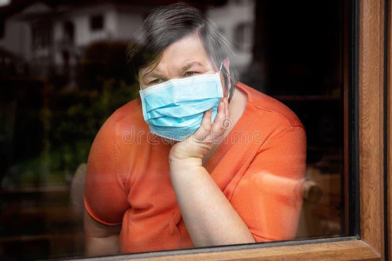 戴外科面罩的精神障碍女性,视窗外 免版税库存照片