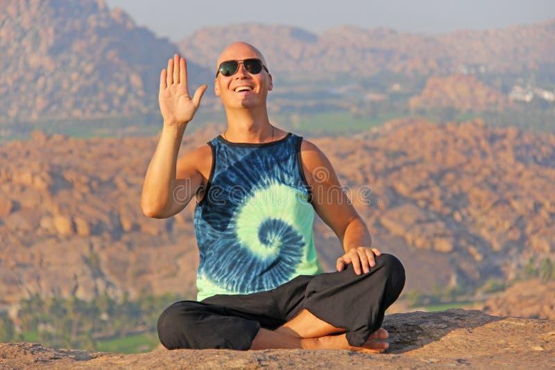 戴太阳镜的一个秃头人在亨比,对Anjaney小山,哈奴曼寺庙坐并且微笑 放松并且休息,单独与自然 米 图库摄影