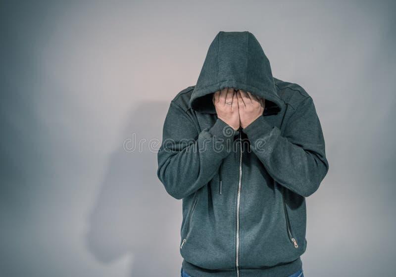 戴头巾夹克的绝望人哭泣,手盖面孔和泪花在眼睛,发光从他的右边的希望光 库存照片