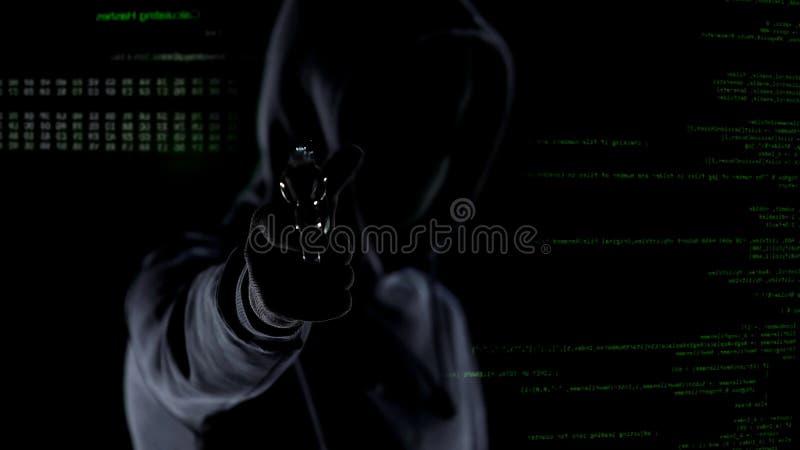 戴头巾男性特写镜头与枪的在生气蓬勃的个人计算机代码前面,射击秘密审议 免版税图库摄影