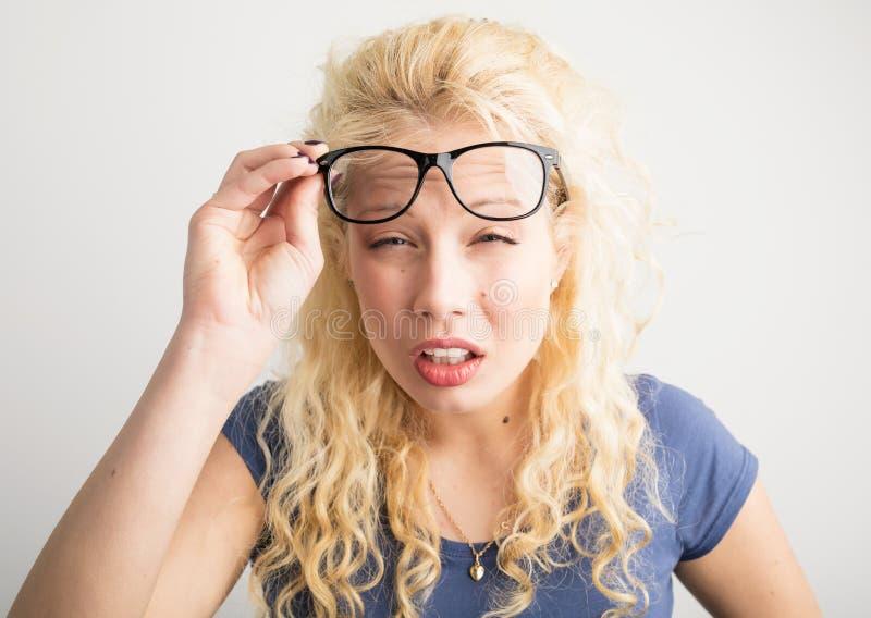 戴她的眼镜的妇女被举罐头` t看见 免版税库存图片