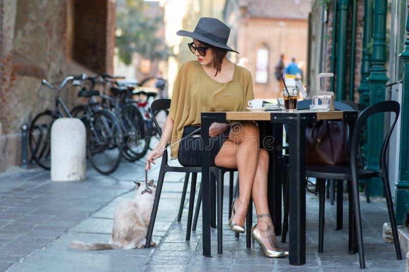 戴帽子和眼镜的一名典雅的意大利妇女拿着在皮带的一只猫 免版税库存照片