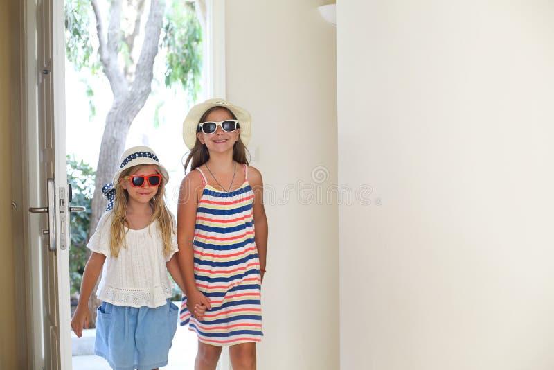 戴帽子和眼镜的两个妹在酒店房间 免版税库存照片