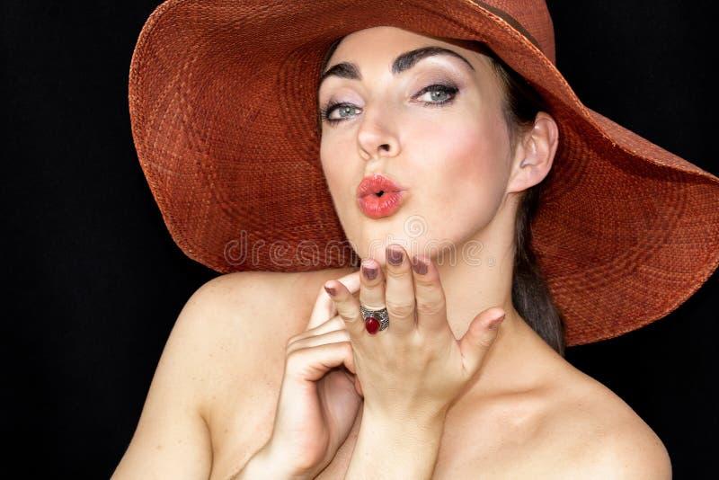 戴帽子的一美丽的年轻女人的画象,她送一个亲吻反对黑背景 图库摄影