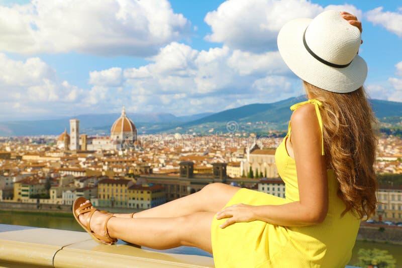 戴帽子的漂亮年轻女子坐在墙上,欣赏意大利托斯卡纳佛罗伦萨的壮丽全景 图库摄影