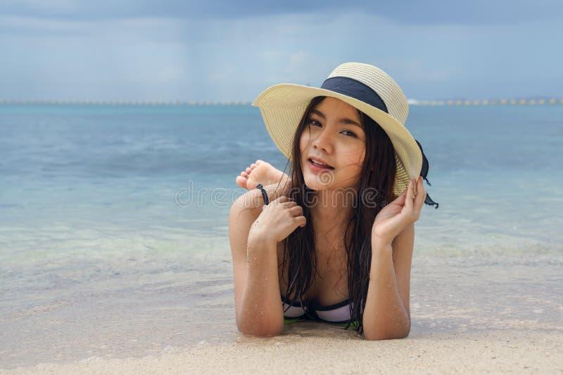 戴帽子的美丽的妇女说谎在海滩 库存照片
