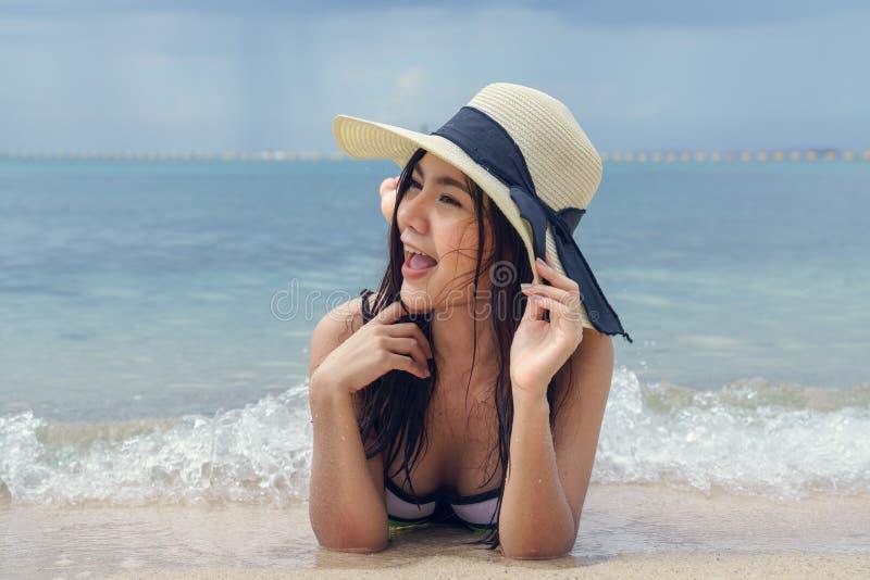 戴帽子的美丽的妇女说谎在海滩 免版税库存照片