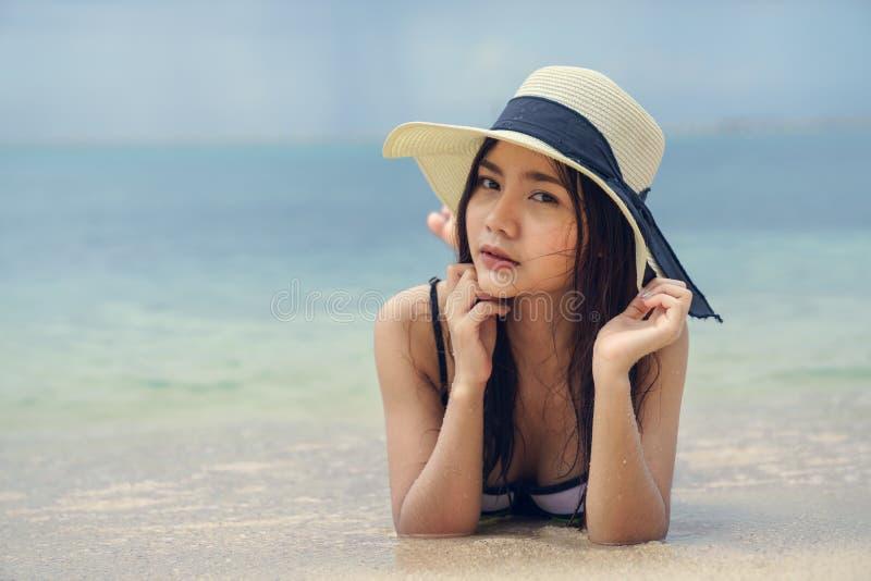 戴帽子的美丽的妇女说谎在海滩 库存图片