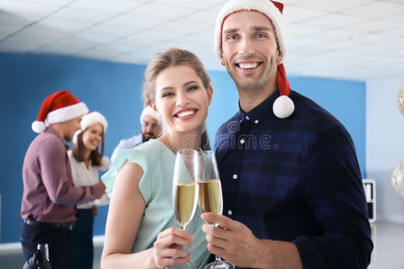 戴庆祝圣诞节的香槟眼镜的年轻人在公司党在办公室 库存照片