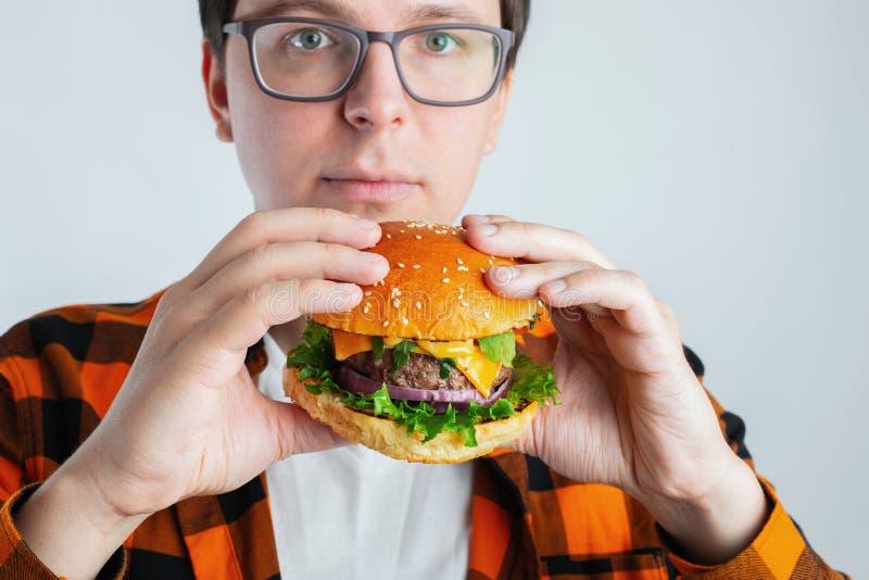 戴拿着一个新鲜的汉堡的眼镜的一个年轻人 一名非常饥饿的学生吃便当 热的有用的食物 暴食a的概念 免版税库存图片
