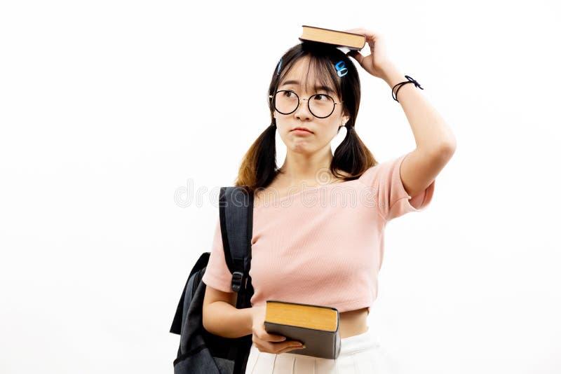 戴拿着堆与袋子的书的时髦眼睛眼镜的年轻亚裔女性学术青少年的学生被隔绝在白色背景 图库摄影