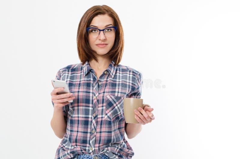 戴拿着杯子智能手机的眼镜的美女 少女饮用的茶和使用小配件 断裂概念 被隔绝的侧视图 图库摄影