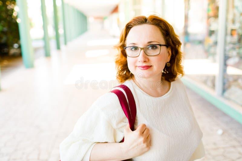 戴摆在柱廊的眼镜的一名妇女 免版税库存图片