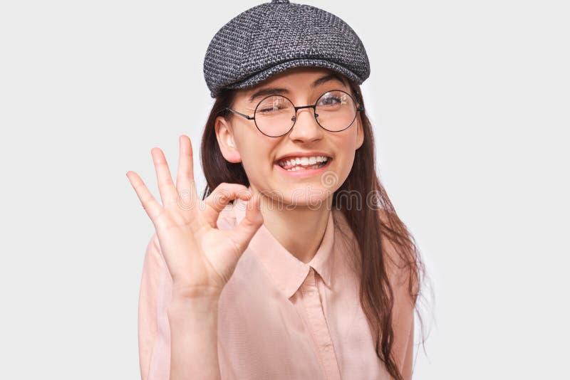 戴时髦灰色盖帽和圆的透明眼镜的满意的年轻女人的接近的演播室图象,显示Ok姿态 免版税库存照片