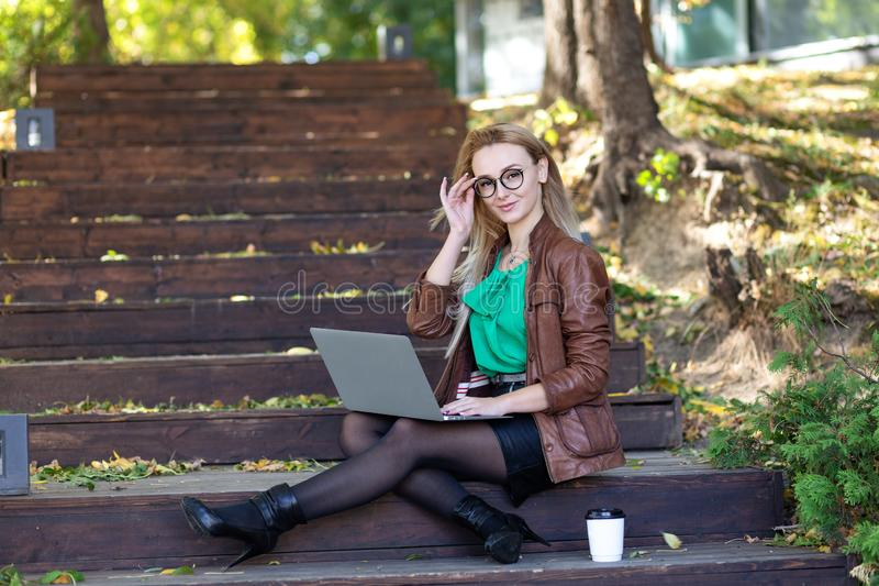 戴时髦的眼镜的年轻东欧白肤金发的妇女坐步在研究有一杯咖啡的膝上型计算机的公园在h旁边 库存图片