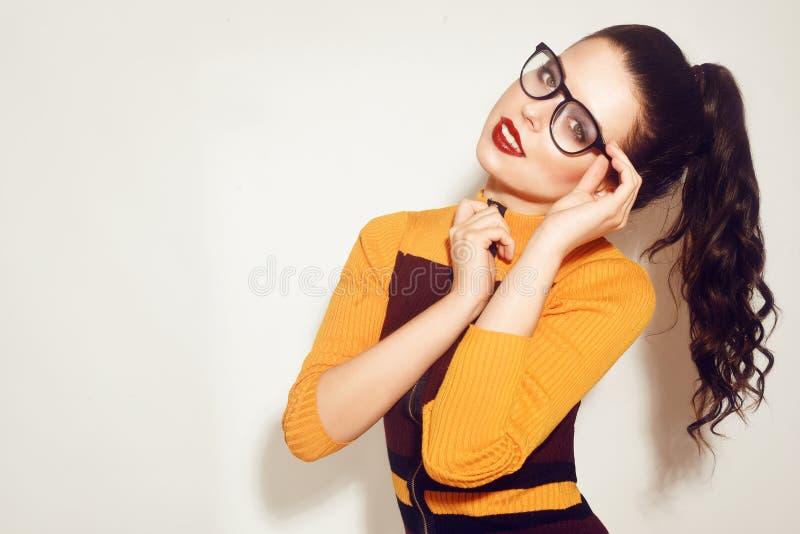 戴时髦的眼镜的秀丽时尚深色的式样女孩 有完善的构成,时髦橙色和红色礼服的性感的妇女 免版税库存图片