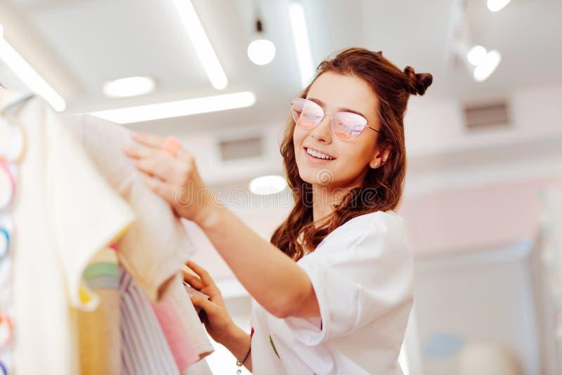 戴明亮的眼镜的放光的女实业家购物在工作以后 免版税库存图片