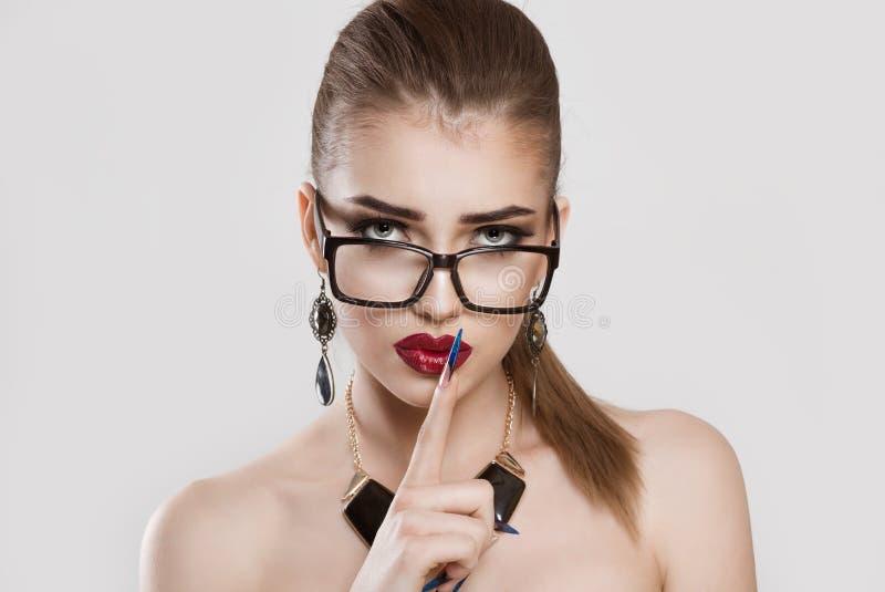 戴显示沈默手势的眼镜的懊恼生气妇女 免版税库存照片