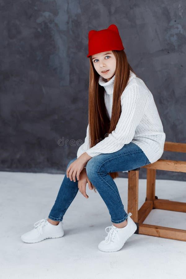 戴有小猫耳朵的美女一个红色帽子 有石楠头发的一个女孩在演播室坐木立方体 免版税库存图片