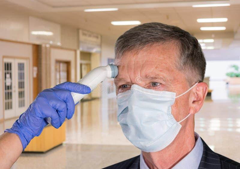 戴有温度的面罩的高级男子在医院检查病毒 库存图片