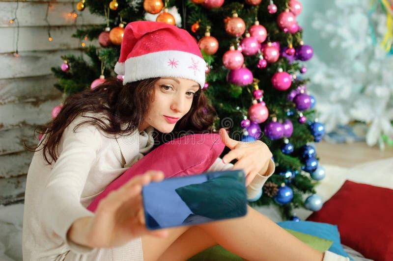 戴桃红色圣诞老人帽子和采取在蓝色手机的俏丽的妇女圣诞节画象selfie在xmas树背景 免版税库存图片