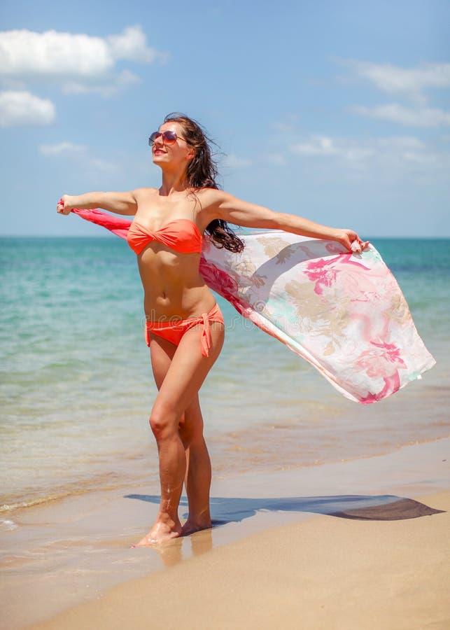 戴橙红比基尼泳装和太阳镜的年轻女人站立在风的海滩挥动的丝绸围巾在她,海背景后 免版税库存照片