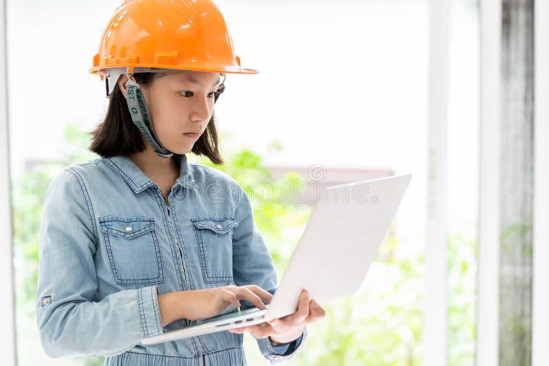戴橙色安全帽或安全帽的亚裔女孩作为建筑师工程师梦想对防护盔甲的未来,逗人喜爱的孩子 图库摄影