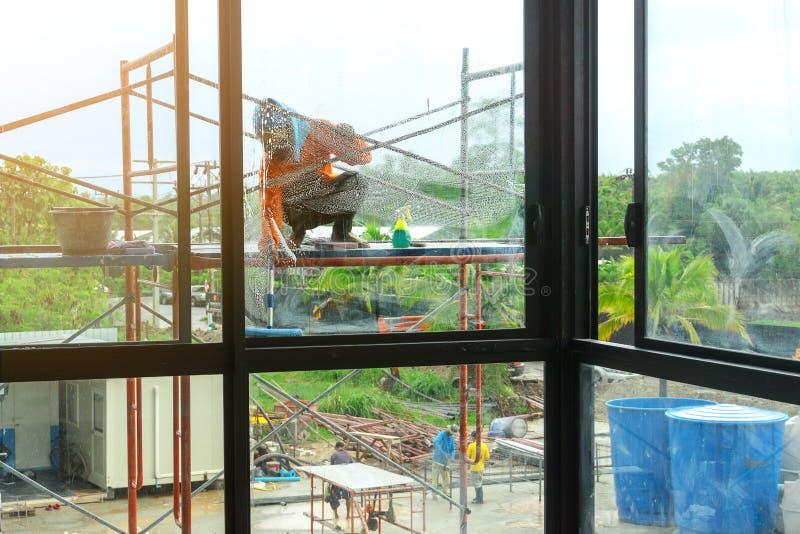戴橙色长袖的T恤杉和蓝色帽子的亚裔女工抹在脚手架的玻璃在buildin之外 图库摄影